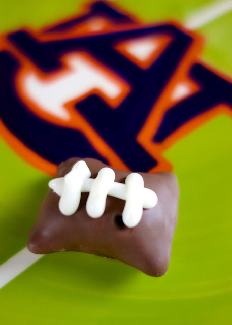 Chocolate Dipped Football Pretzel Bites - easy no-bake football party food! SO easy and SO adorable!!! Tastes like a butterfinger. Peanut Butter filled pretzels, chocolate candy coating, white candy melts and a squeeze bottle. A must for tailgating!
