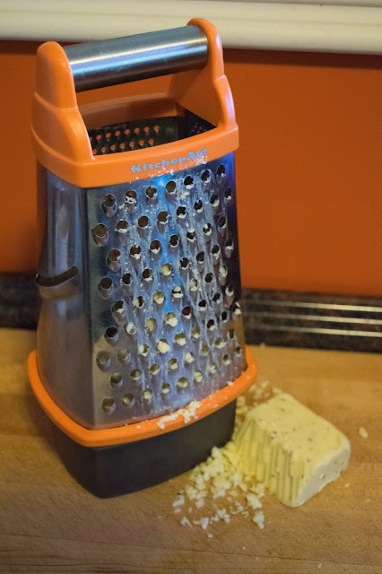 A picture of a cheese grater, on a counter, with a half-grated block of truffled cheddar cheese.