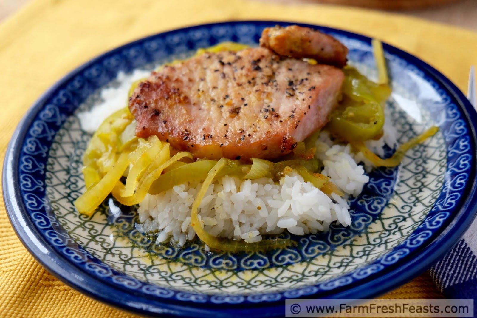 a plate of pork chops baked with curried green tomatoes and onions served over rice