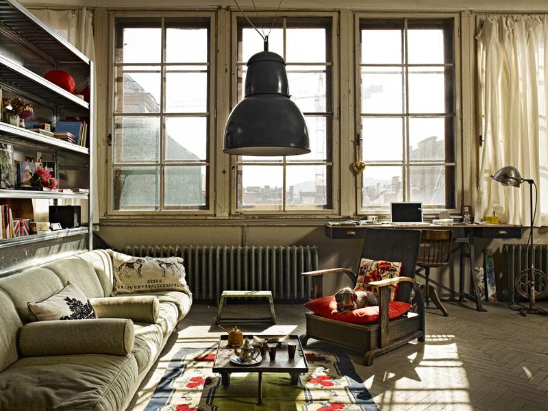 Salón con grandes ventanas en un mini loft vintage- industrial