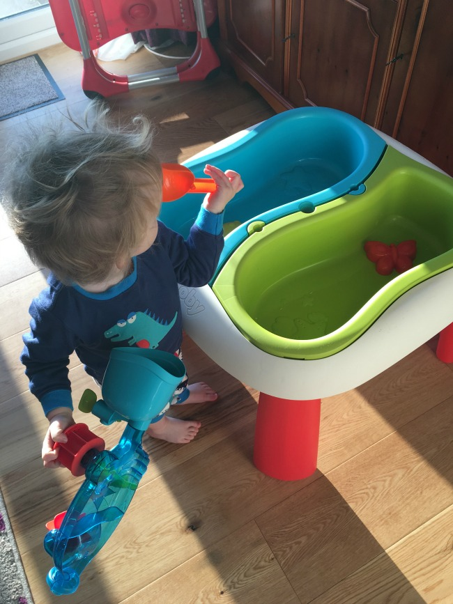Toddler holding scoop and water wheel looking at each bit intently