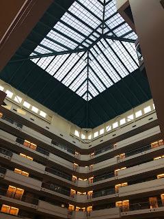 Glasstak i en høy bygning sett fra en lavere etasje.
