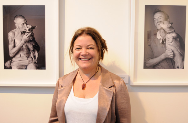 Portrait of Linda Warlond at her 'Love is the Colour' exhibition, her pictures in background , at The Depot, Danks Street Sydney.