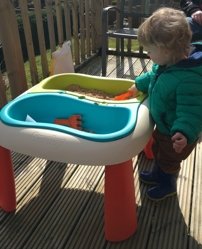 Messy Fun With The Smoby Water and Sand Table Toddler playing with sand on decking in the sun