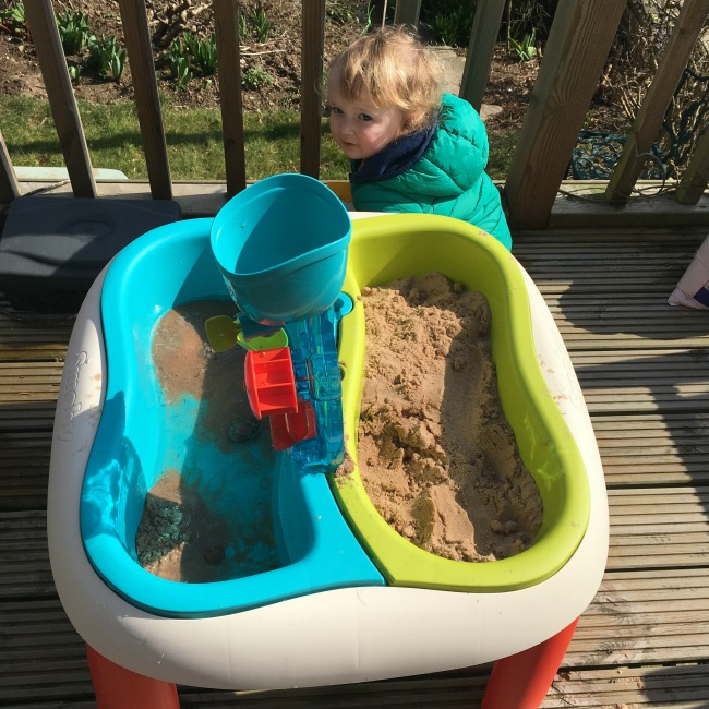 tray with and, tray with water and sand and toddler crouched down