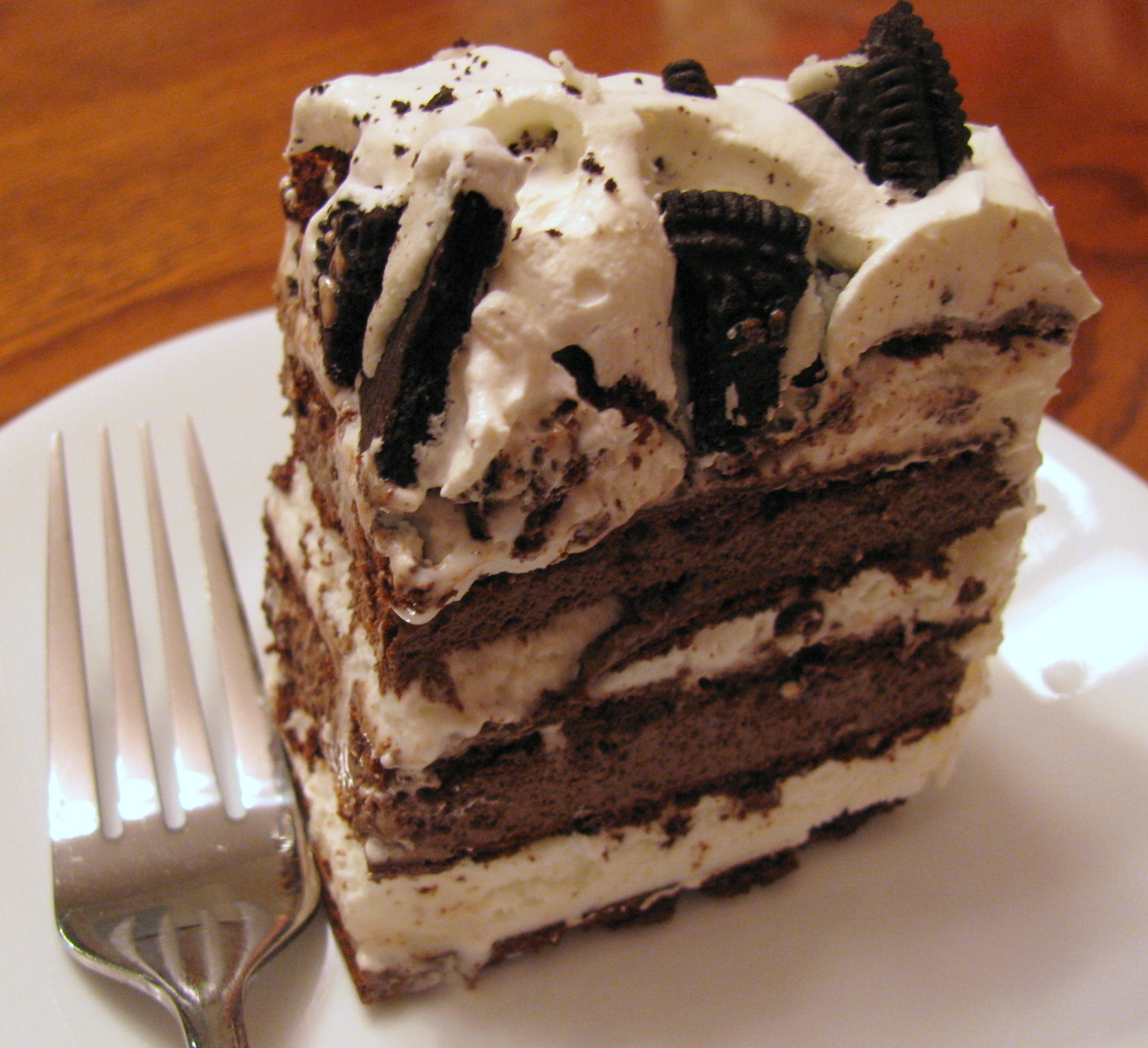 This no bake ice cream cake recipe can be prepared in about 5 minutes (plus freezing time). Layered w/ chocolate ice cream, vanilla ice cream sandwiches, hot fudge, and crushed Oreo cookies AND topped off w/ whipped cream & more Oreos, it will knock your guests' socks off!