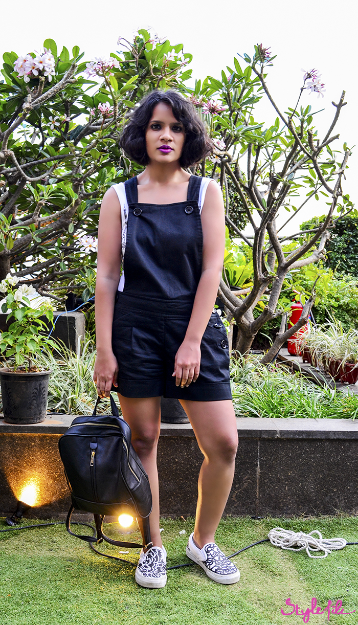 Style File fashion blogger Dayle Pereira wears black dungarees over a whitesuit with purple lips, a messy bob, sneakers and a backpack at Lakme Fashion Week