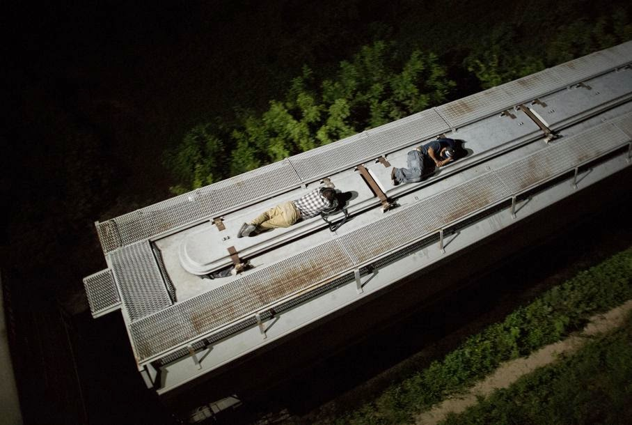 In this Aug. 26, 2014 photo, Central American migrants sleep atop a moving freight train as it heads north from Arriaga toward Chahuites, Mexico.