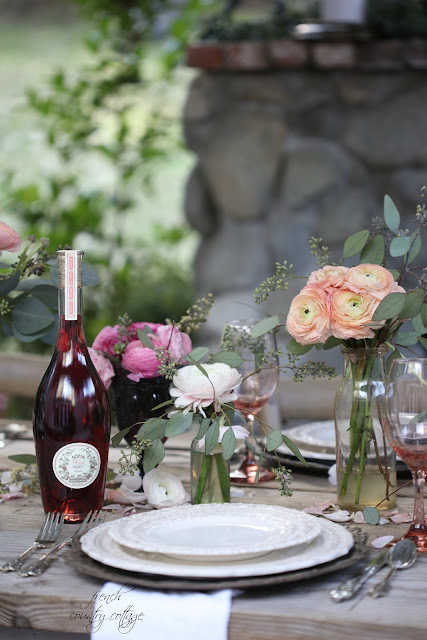 Place settings, wine and flowers on table