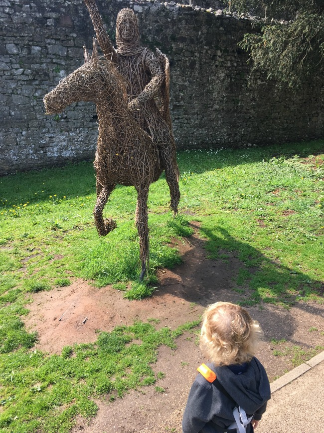 toddler looking at a wicker knight on horseback