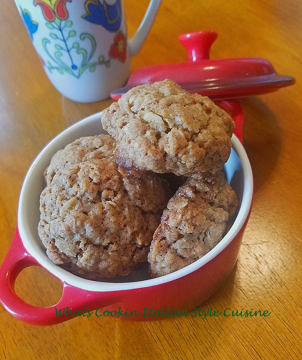 These old fashioned oatmeal cookies are over 100 years old made from scratch a crisp cookie in a red cover dish with vintage bird design coffee cup.