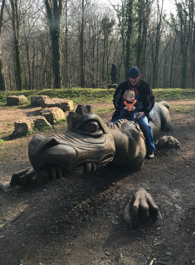 carved dragon with man and toddler sat on it and bat sculpture behind