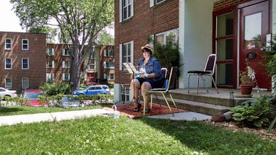 me playing the ukulele; my ukulele is light blue and I am wearing jean shorts, a tank top, a jean jacket, and a hat; in front of me is a music stand and I am sitting in front of an apartment complex