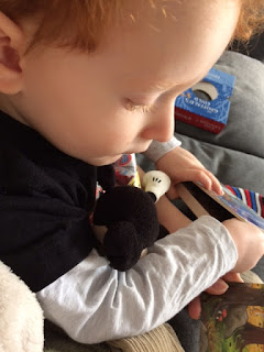 Toddler reading the book and holding a Mickey toy