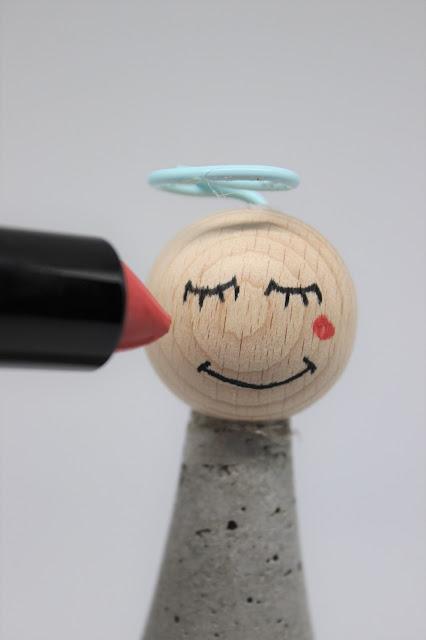 Mit einem Lippenstift werden rote Punkte auf die Holzkugel gemalt.