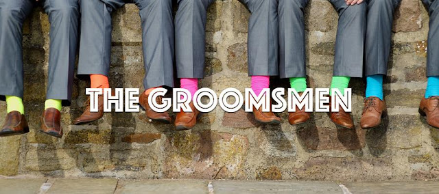 The Groomsmen sitting on a wall showing off their brightly coloured socks