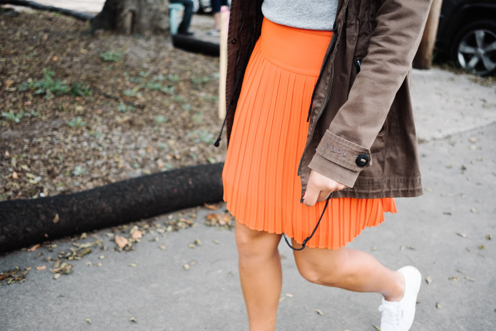 Priya the Blog, Nashville style blog, orange pleated skirt, ban.do I Like Sports pin, white Superga trainers, gray crewneck sweatshirt, girly sporty outfit