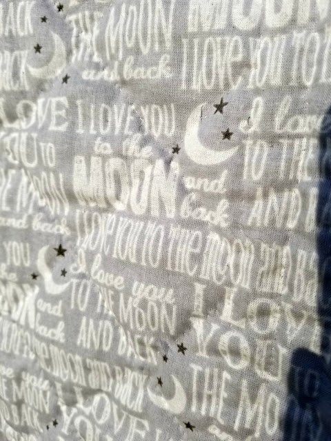 "The backing fabric print is appropriate: ""I love you to the moon and back."""