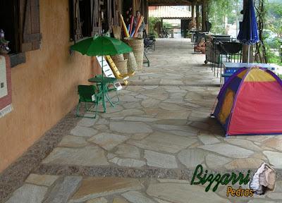 Execução da construção rústica já com o terraço com os pilares de madeira pronto, com o piso de pedra caco de São Tomé pronto e na alvenaria de bloco de cimento as janelas de madeira com os batentes de dormente de madeira com a parede pintada com terra e a loja sendo inaugurada.