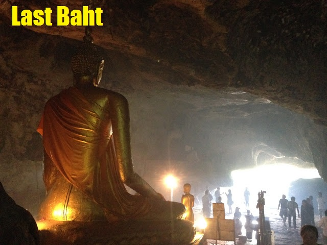 a Buddha statue inside a dark cave temple in Kanchanaburi, Thailand