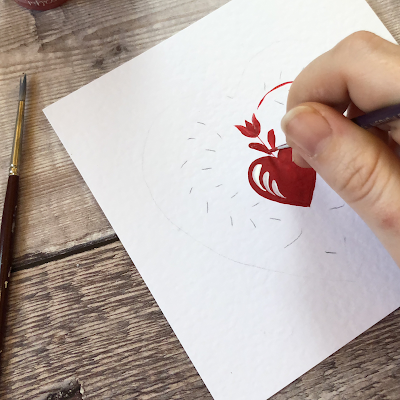 Red heart and folk art tulip being painted on to a white greetings card