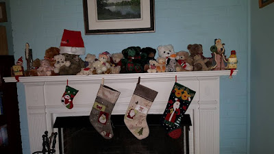 mantle with teddies, two old santas, Whitman elves, and stockings
