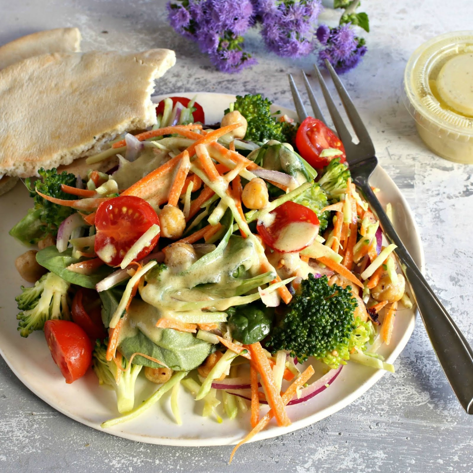 Coleslaw with crispy chickpeas, broccoli and tomatoes in a mustard tahini dressing.