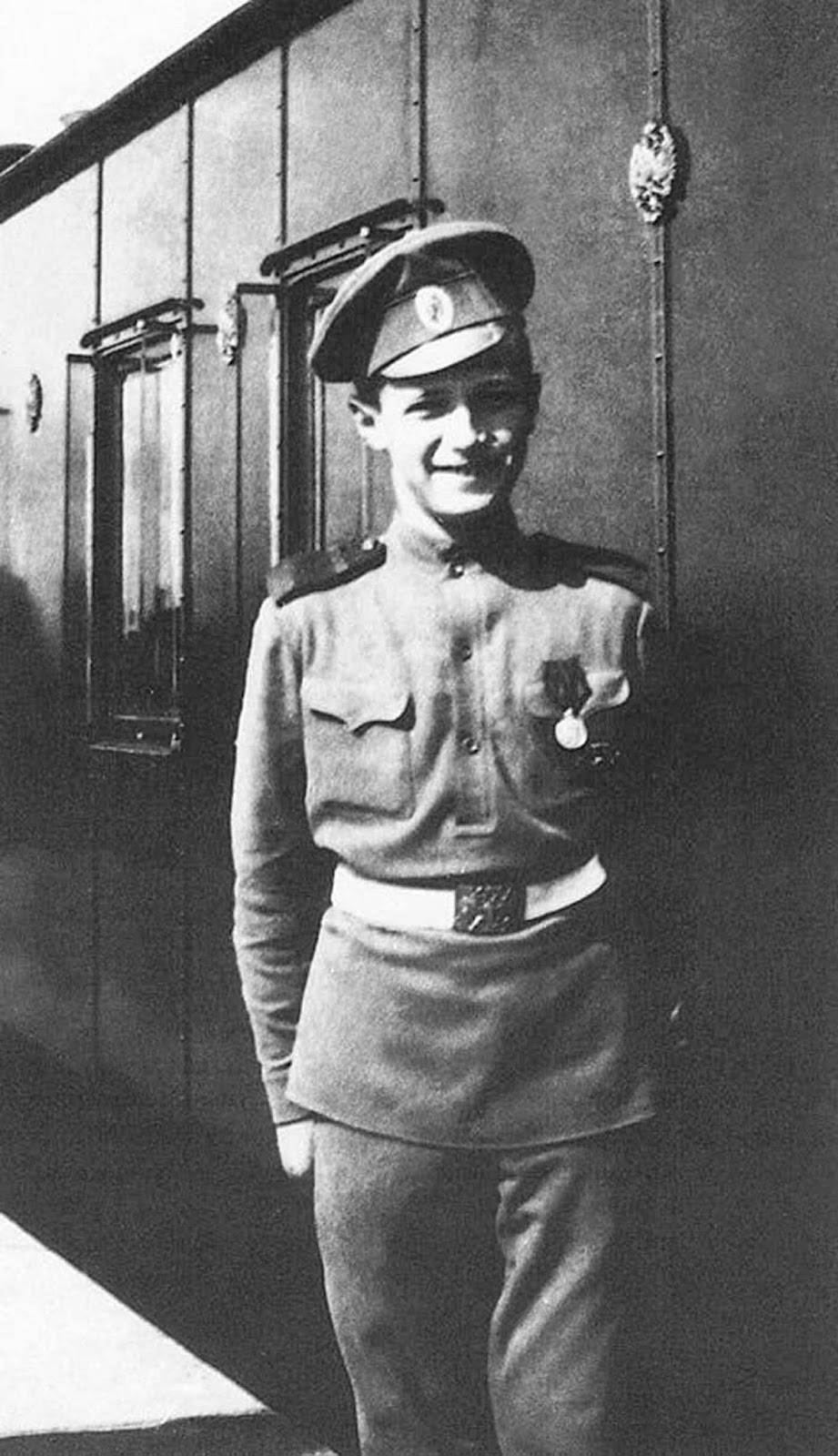 A smiling Tsesarevich Alexis standing on the platform in front of the Imperial Train.