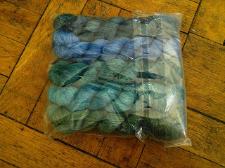A clear plastic bag containing 5 small skeins of yarn, ranging from dark blue to green in a gradient.