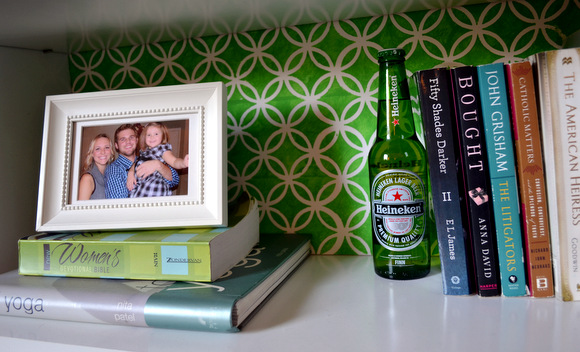 This book shelf is decorated cute with picture frames and empty beer bottles.