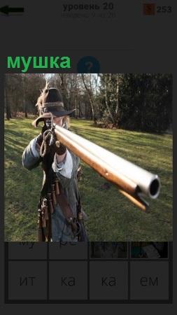 Охотник поднял ружье и целится мушкой в цель на лесной поляне