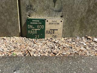 """Ein Schild mit der Aufschrift """"Grubenwasser"""" hängt am Boden"""