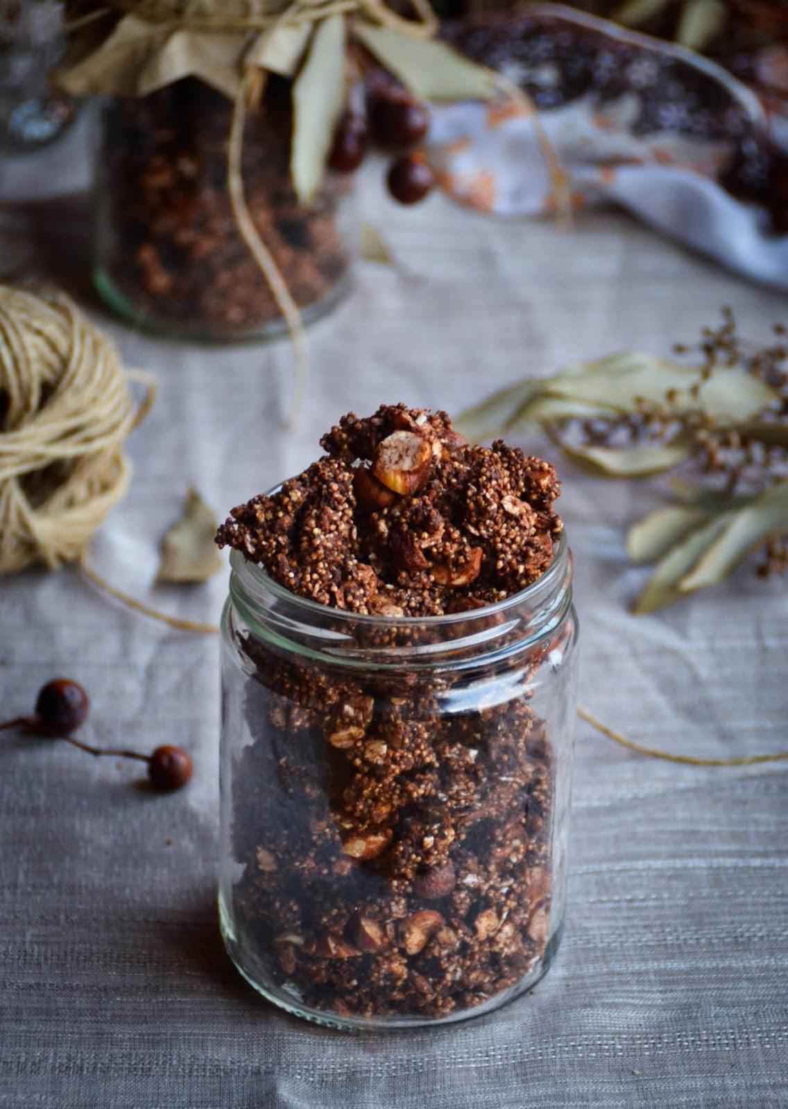 Tarro abierto para regalo granola ferrero rocher sin gluten, fondo madera vieja, hojas eucalipto y ramas secas decorativas, cordón de esparto, velas encendidas