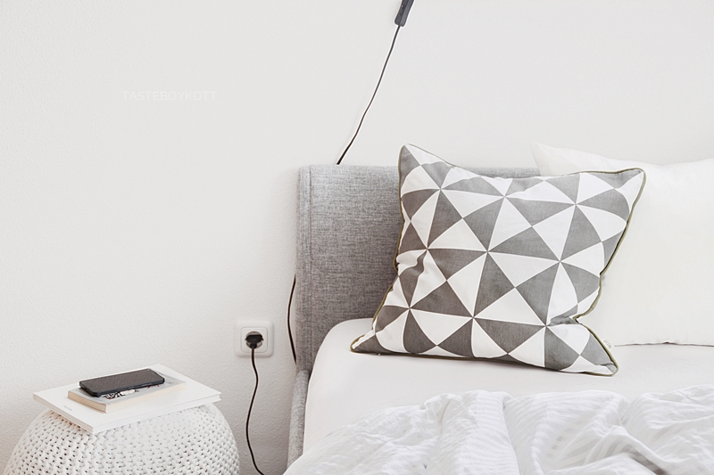 white and light grey bedroom with ferm living geometry pillow, pouf, headboard | Tasteboykott