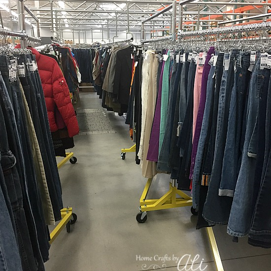 jeans and other clothes on racks to restock thrift store