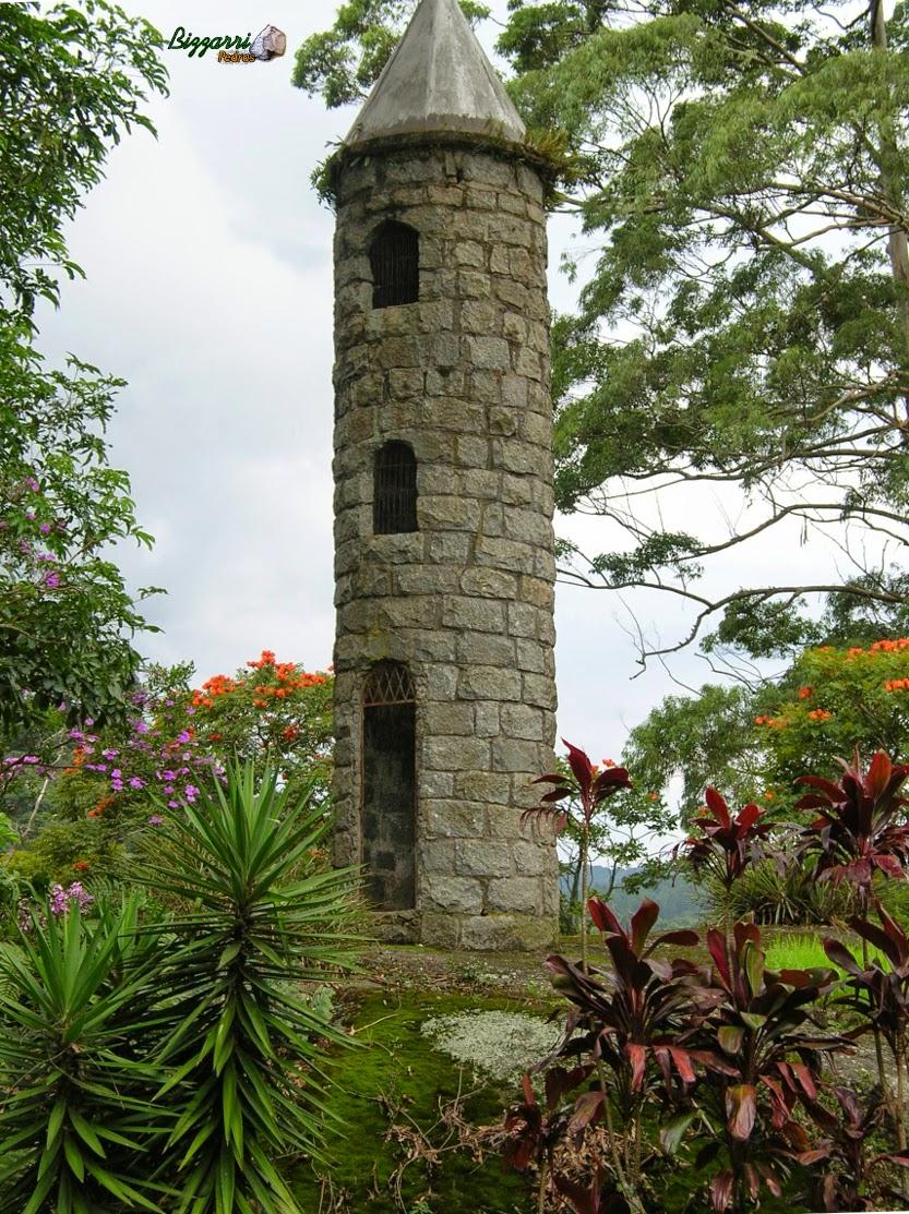 Detalhe da torre de pedra com parede de pedra com pedra do tipo folheta e a execução do paisagismo.