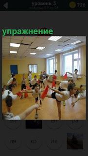 В спортивном зале дети делают разные упражнения, занимаясь гимнастикой