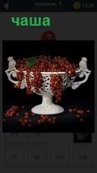 Красная смородина гроздями лежит в чаше и свисает по сторонам ветками с ягодами