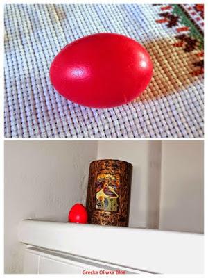 Na białej  półce w kącie znajduje się czerwone jajko obok sakralnej figurki.