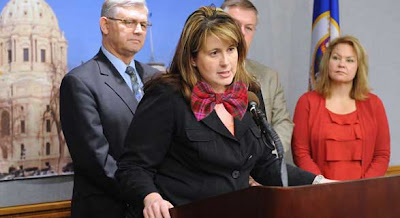 Photo of Amy Koch speaking at a podium, wearing a dark suit with a Photoshopped bright pink plaid bow tie