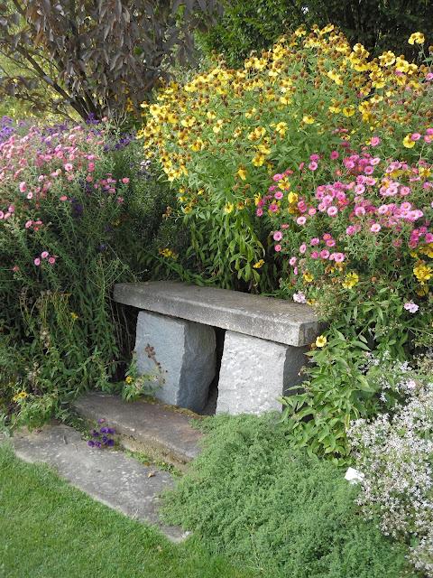 kamienna ławka wśród kwiatów