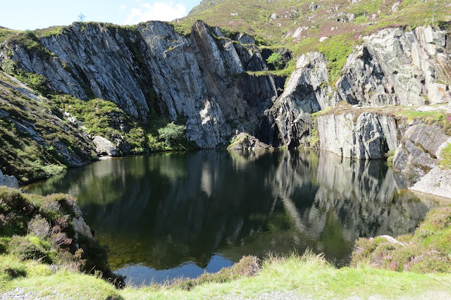 A water filled quarry, surrounded by steep rock faces and occasional grassy ledges.
