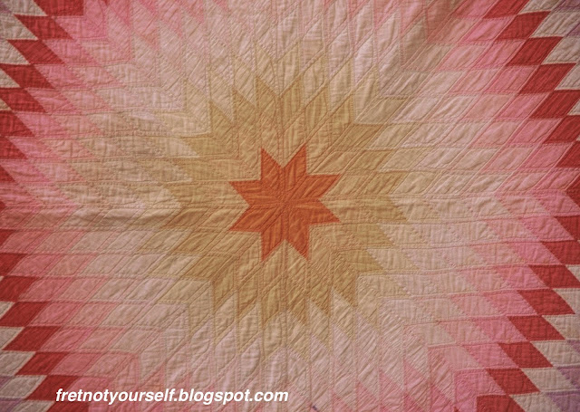Center of Lone Star quilt in yellow, orange, pink and red solids made in 1920s Oklahoma.