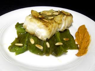 Bacalao confitado con pimientos verdes asados, romesco y piñones