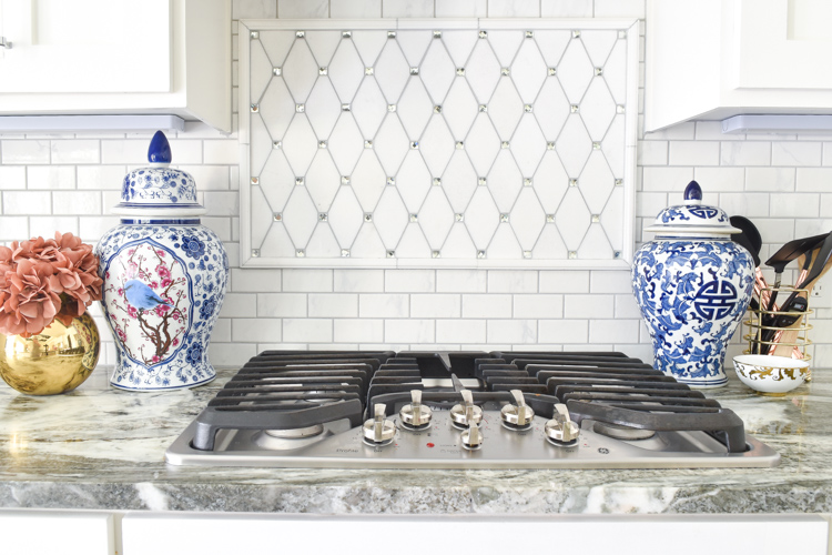 White shaker cabinet kitchen with marble countertops, blue and white ginger jars, and lucite cabinet hardware and pulls. #whitekitchen #brightkitchen #shakercabinets