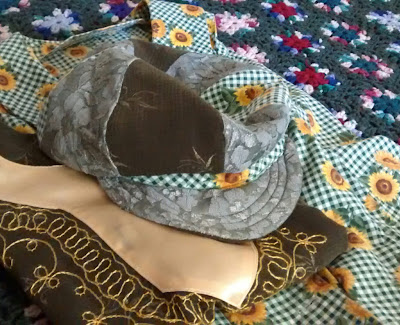 'Newsboy' style hat with crown assembled from varigated panels of sunflowers-on-green-check, pale green lace over pale green backing fabric and dark green-on-green embroidered fabric. The hat band is bias-cut sunflower-and-check. The visible upper bill is pale green lace over backing fabric. The hat sits atop a folded sleeveless dress of the sunflower-and-green-check print and a dark-green embroidered tunic with a yellow-gold embroidered and appliqued neckline border
