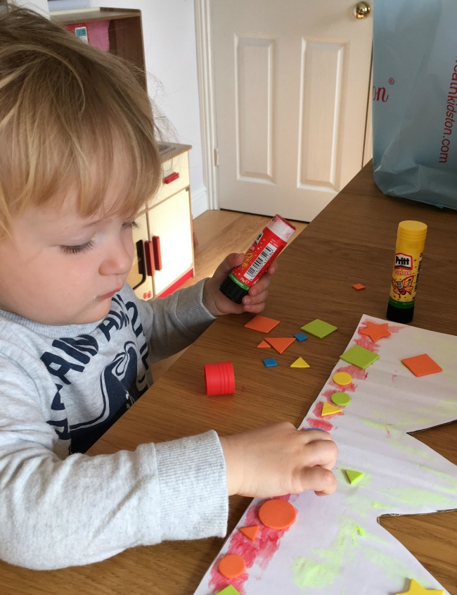 toddler sticking shapes to a piece of card