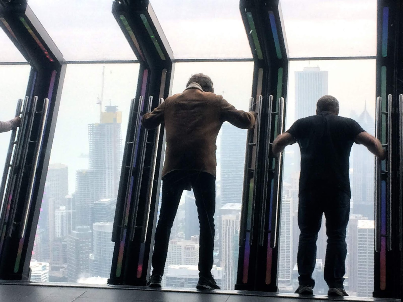 Two people holding on to the window, tilting at 45 degrees in a tower