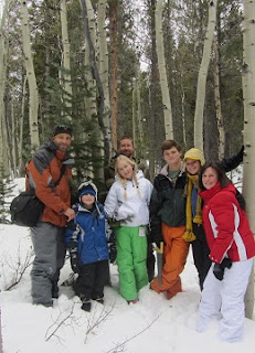 Family of seven cutting their Christmas tree in the forest and snow all around.