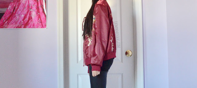 Wine red silky satin floral embroidered oversized bomber jacket from SheIn, worn with a plunging lace-up bodysuit and leather-paneled pants.